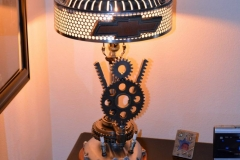 V8 themed lamp, motorcycle cover for base, Plymouth hubcap, Chrysler Cordoba hood ornament as finial.
