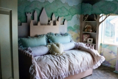 Castle daybed with matching tree shelves and mural on all walls.
