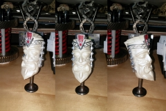 V8 tiki shift knob, painted with pearl white, emblem and headdress painted in silver with red infill in the emblem background.